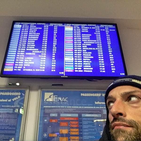 uomo in aeroporto davanti schermo voli
